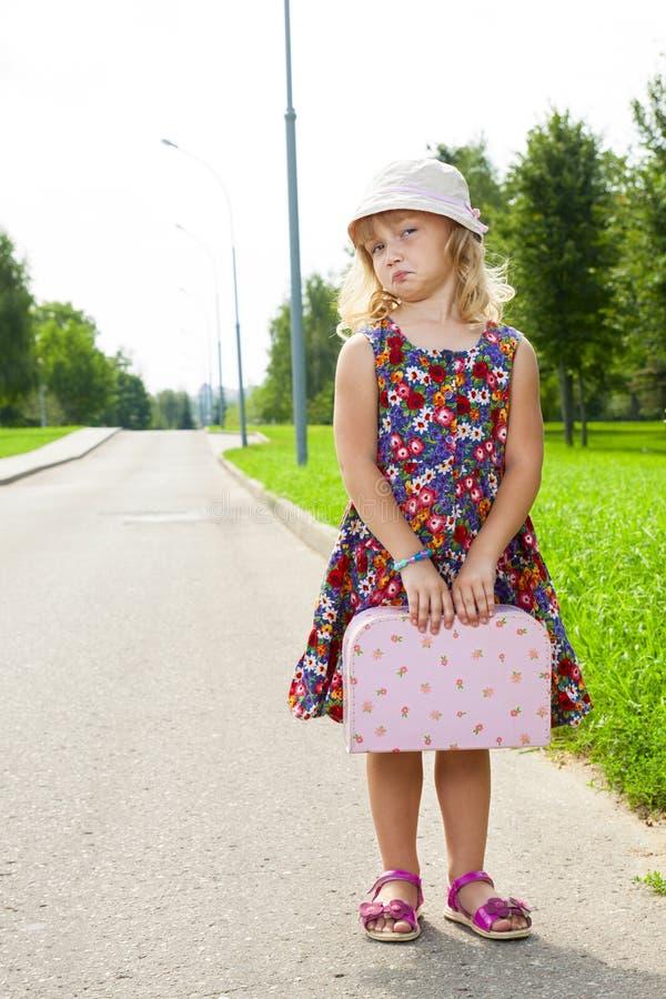 带着站立在路的手提箱的女孩 库存图片