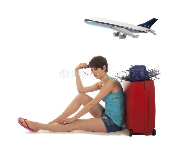带着等待乏味延迟班机的手提箱的女孩 免版税库存照片
