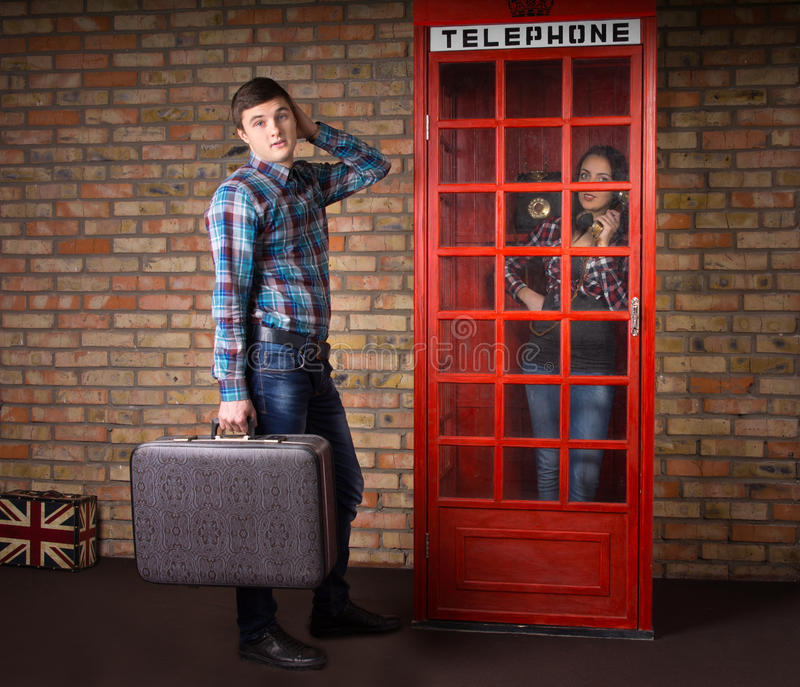 带着等待在电话亭的手提箱的人 免版税库存照片