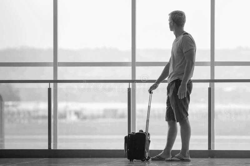 带着等待飞机的手提箱的人在终端机场 免版税库存图片