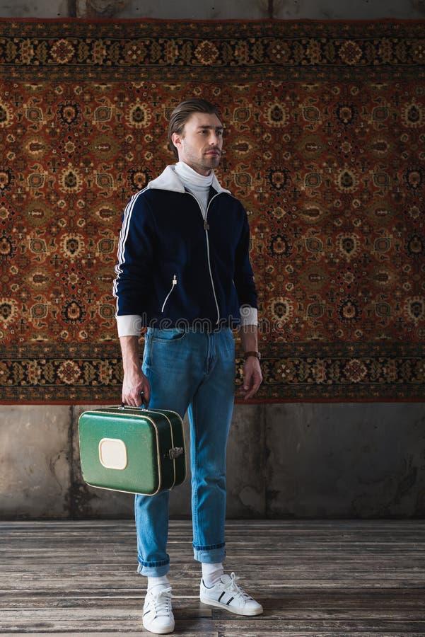 带着葡萄酒小的手提箱的帅哥在地毯垂悬前面 免版税库存照片