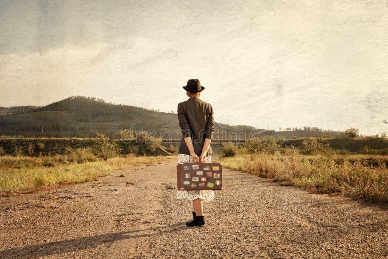 带着葡萄酒旅行手提箱的妇女在老路 在图象s的照片 免版税库存图片