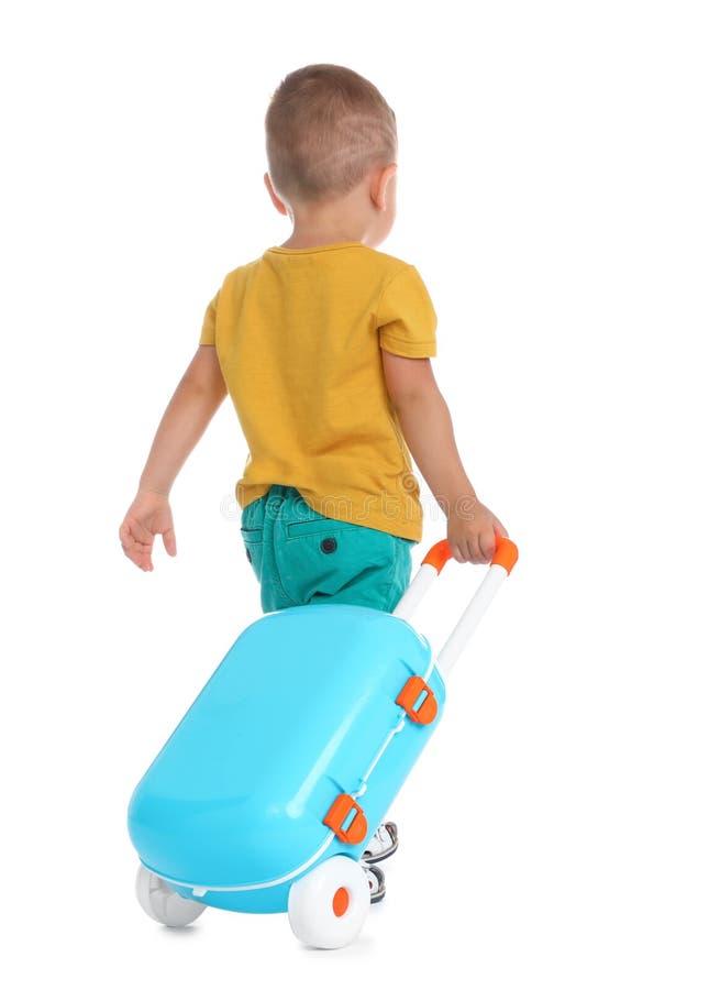 带着蓝色手提箱的逗人喜爱的小男孩在白色 库存图片