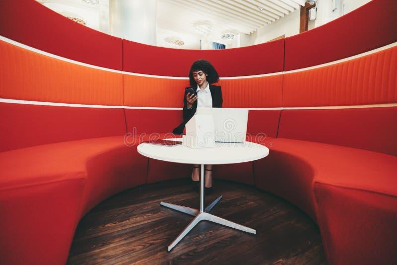 带笔记本电脑和红沙发的混血女人 免版税图库摄影