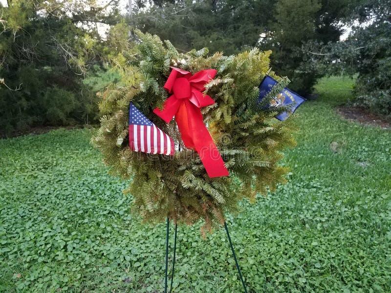 带红蝴蝶结和美国退伍军人国旗的绿色花圈 库存照片