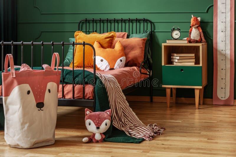 带绿色墙壁和橙色寝具的可爱卧室室内福克斯主题 免版税库存照片