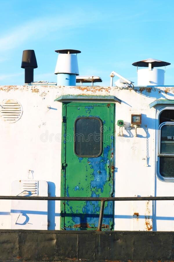 带绿门的生锈船 库存图片
