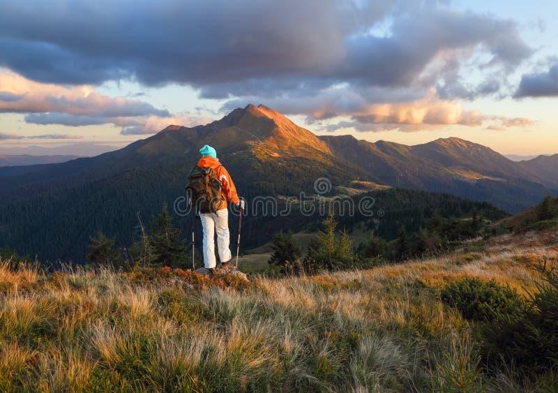 带背包的快乐游客住在山上 秋阳日 穿运动服的女孩 山景 免版税图库摄影