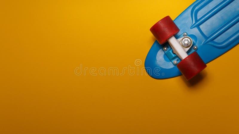 带蓝色甲板和黄色背景红色轮的带复制空间的顶视图的滑板巡洋舰 体育生活方式的概念 库存照片