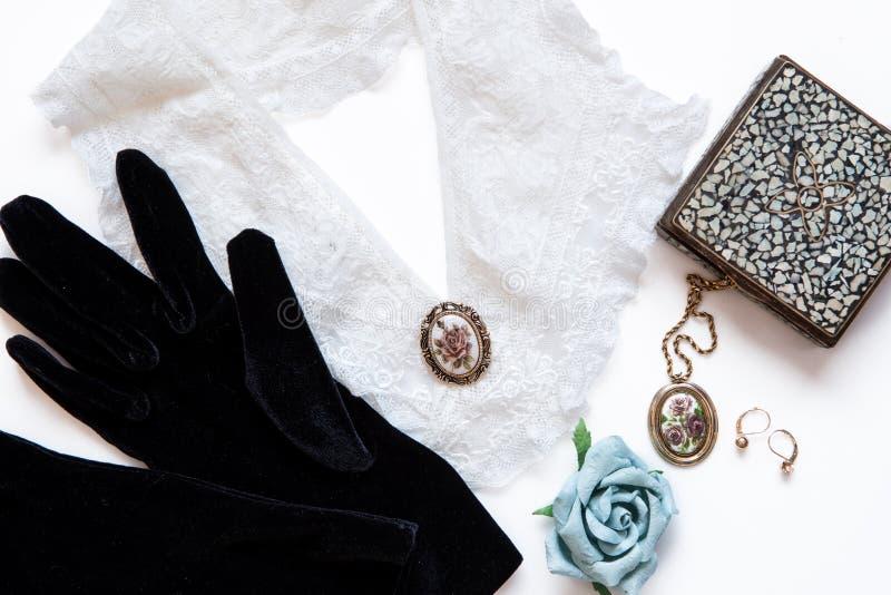 带蕾丝领、珠宝、盒子和纸玫瑰的天鹅绒手套 古董静物 从顶层看旧时装概念 免版税库存图片