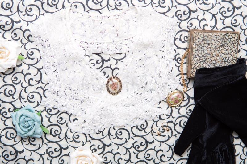 带蕾丝领、珠宝、盒子和纸玫瑰的天鹅绒手套 古董静物 从顶层看旧时装概念 免版税库存照片