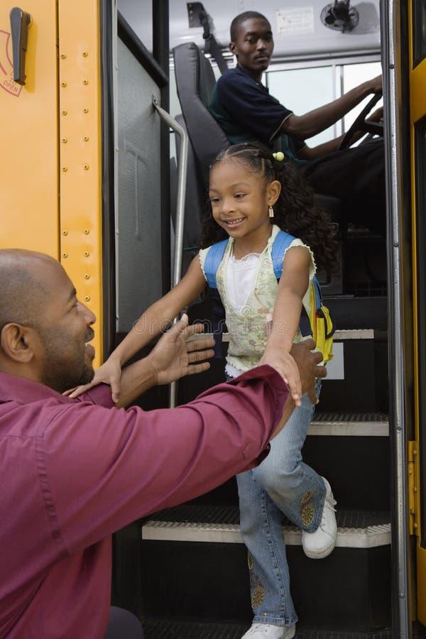 带走女儿的父亲在公共汽车站 免版税库存图片