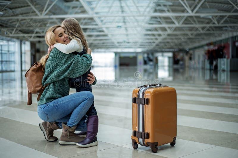 带走孩子的高兴的母亲在机场 免版税图库摄影