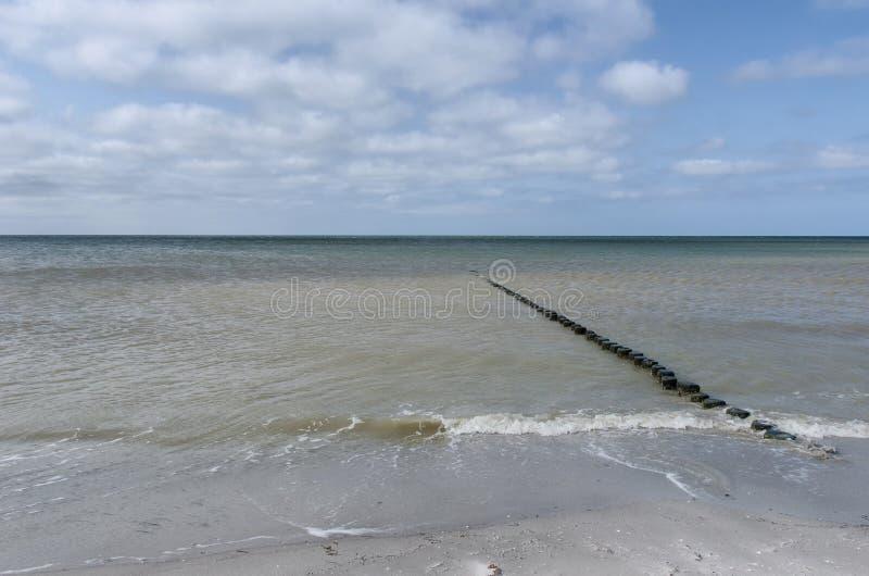带领入有多云天空的海的木岗位行  免版税图库摄影