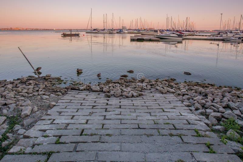 带领入有小游艇船坞的港口的砖道路日落视图在背景在伯灵屯,安大略中 免版税图库摄影