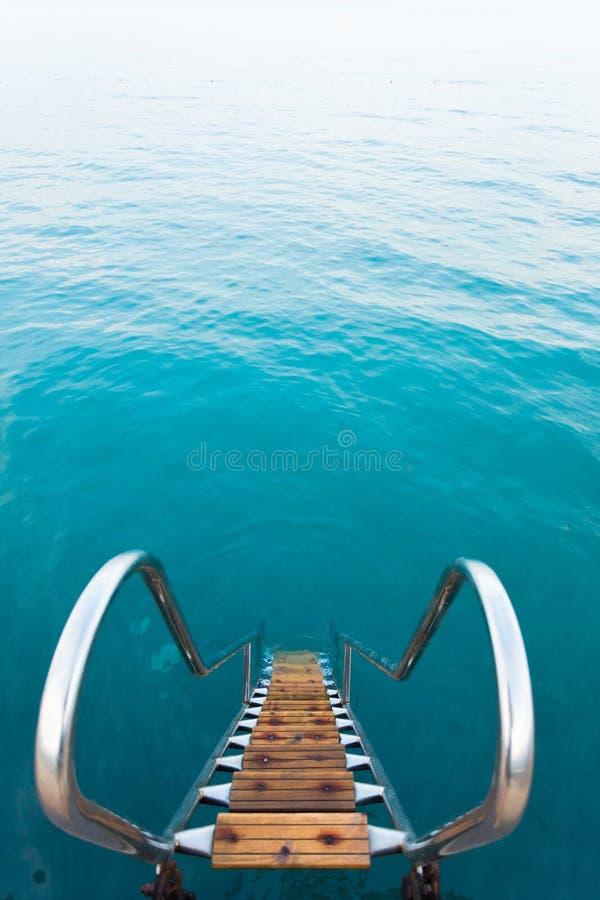 带领入海的刷新的水晶水的梯子 库存照片