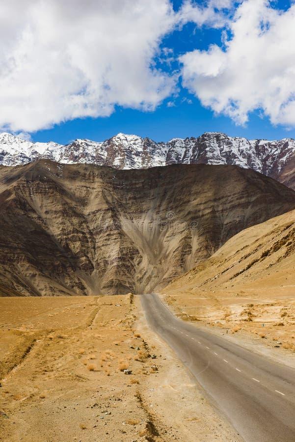 带领往雪加盖的山的空的路 免版税图库摄影