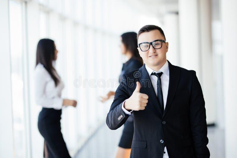 带领我的队成功 在微笑聪明的便衣的英俊的年轻商人保留赞许和,当tal时他的同事 免版税库存图片