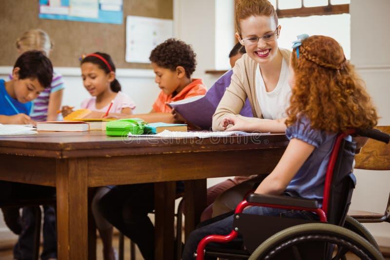 帮助一个残疾学生的老师 免版税库存照片