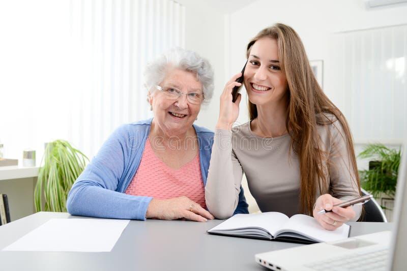 帮助一名老资深妇女的少妇在家做文书工作和管理程序与便携式计算机 免版税库存图片