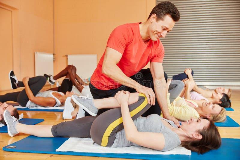 帮助与体操锻炼的健身教练员 免版税库存照片