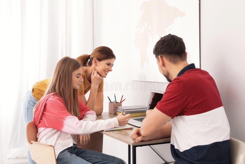 帮助他们的有家庭作业的父母少年女儿 免版税库存照片