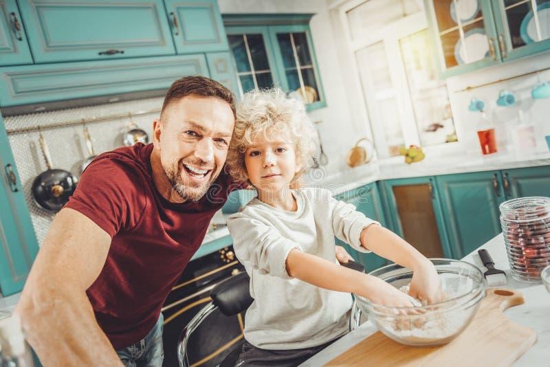 帮助他们的母亲的父亲和儿子,当揉饼的时面团 免版税库存照片