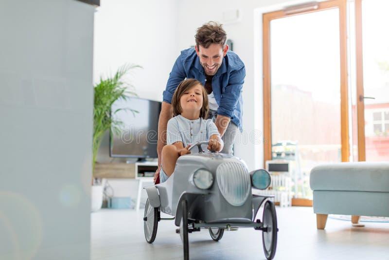 帮助他的儿子的父亲驾驶玩具贩卖汽车 免版税图库摄影