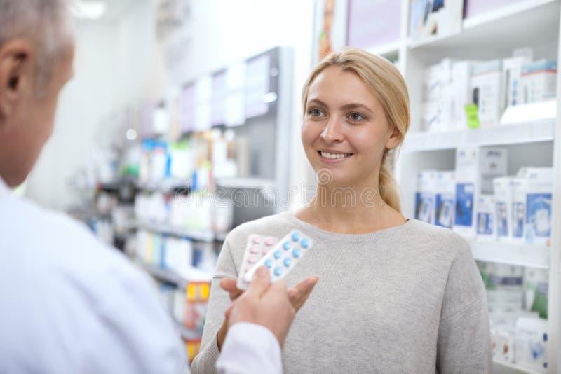 帮助他的女性顾客的成熟药剂师 免版税库存照片