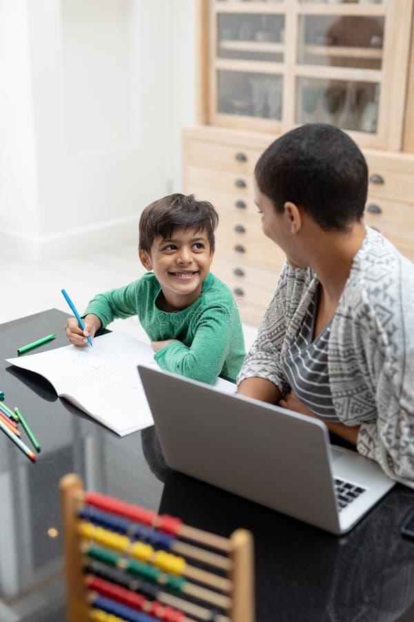 帮助他的有他的家庭作业的母亲儿子在桌上 库存图片