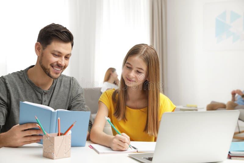 帮助他的有家庭作业的父亲少年女儿 免版税库存照片