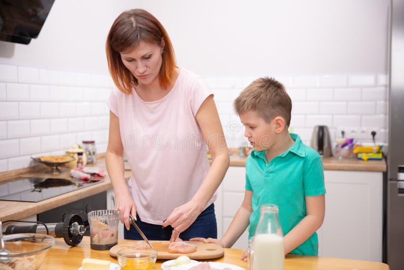 帮助他的有烹调的小男孩母亲在厨房里 免版税图库摄影