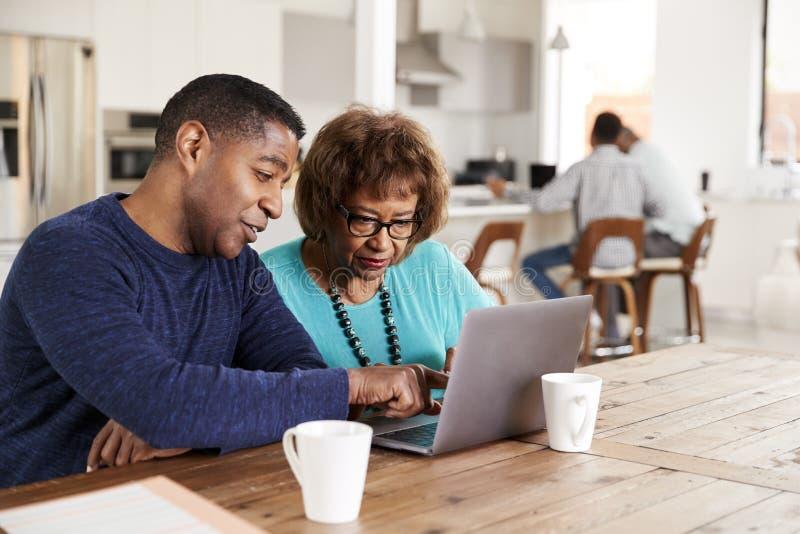 帮助他的母亲的中间年迈的非裔美国人的人在家使用手提电脑,关闭  库存图片