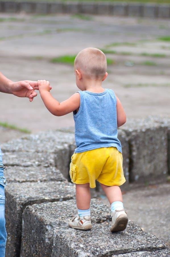帮助他的男孩一点母亲走 库存图片