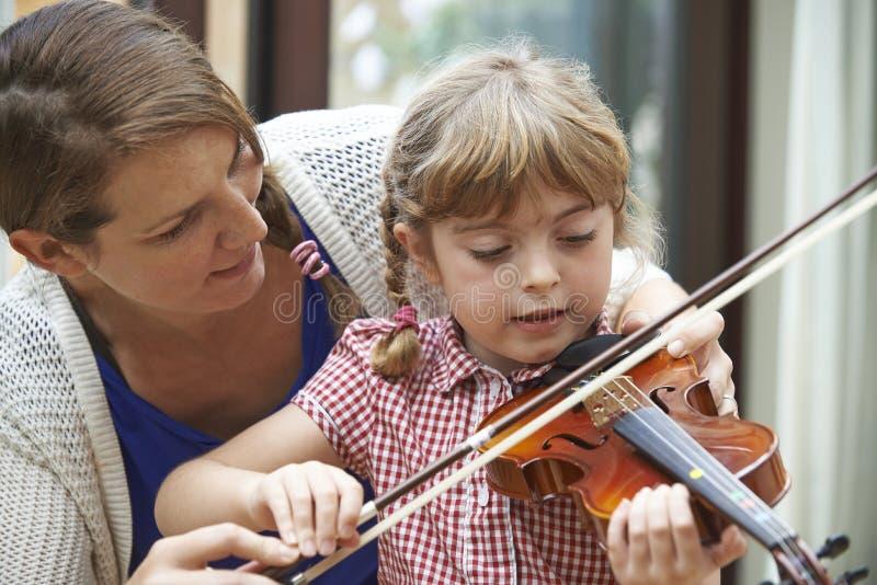 帮助在小提琴课的老师幼小母学生 免版税图库摄影