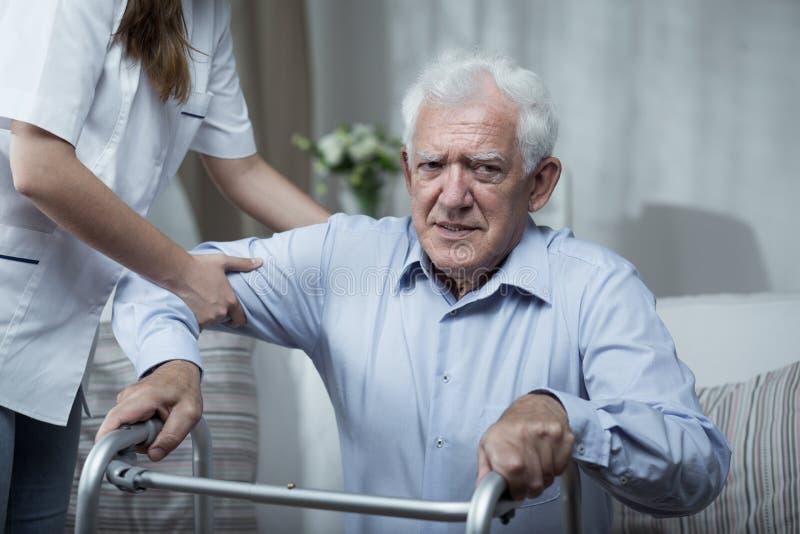 帮助失去能力的老人的生理治疗师 免版税库存图片