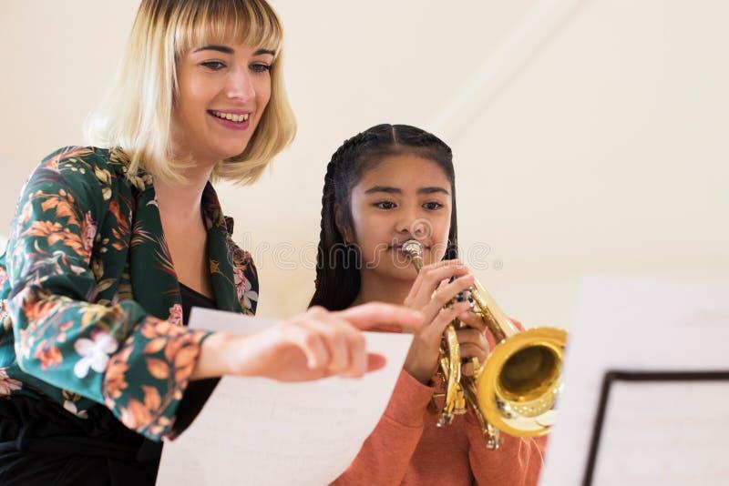 帮助女学生的老师弹在音乐课的喇叭 免版税库存图片