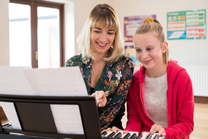 帮助女学生的老师弹在音乐课的钢琴 免版税库存照片