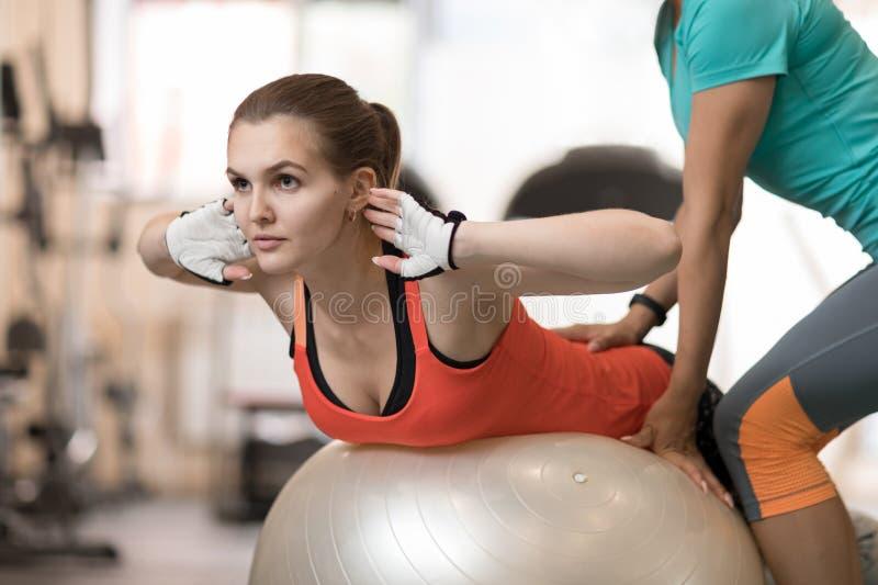 帮助女孩的健身教练员做在健身房的背部锻炼. backarrow, 健身.