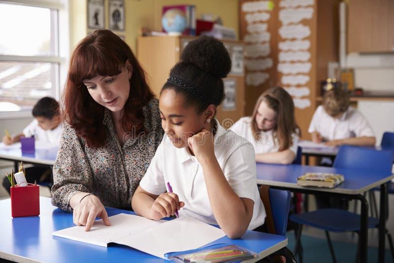 帮助女小学生的小学教师在她的书桌 免版税库存照片
