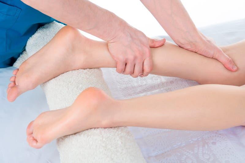 帮助女性患者的医生生理治疗师,当给运作的行使按摩患者的腿在理疗的屋子里,时 免版税库存图片