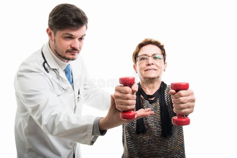 帮助女性患者的男性医生与哑铃一起使用 库存图片