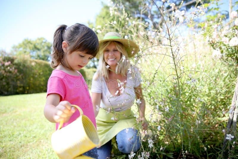 帮助她母亲从事园艺的小女孩 免版税库存照片