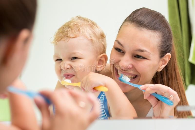帮助她的儿子的美丽的母亲刷牙在卫生间里 库存图片