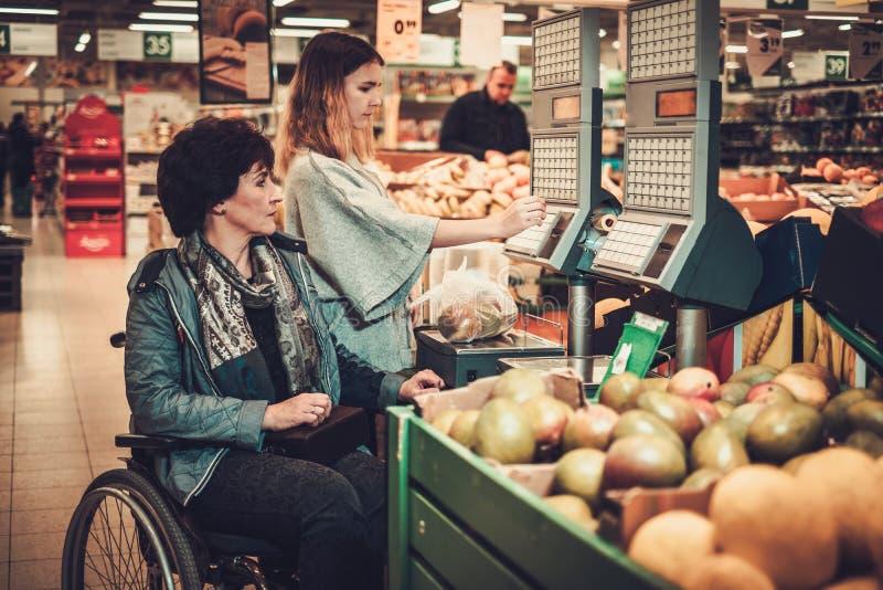 帮助她的在轮椅的女孩残疾mothter在杂货店 免版税库存照片