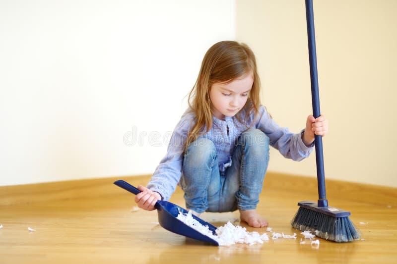 帮助她的妈妈的可爱的女孩清扫 免版税库存图片