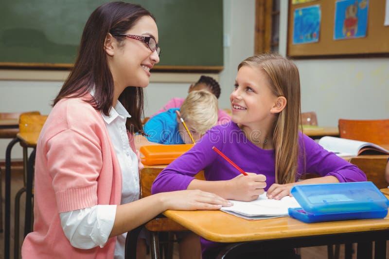 帮助她的学生的愉快的老师 图库摄影