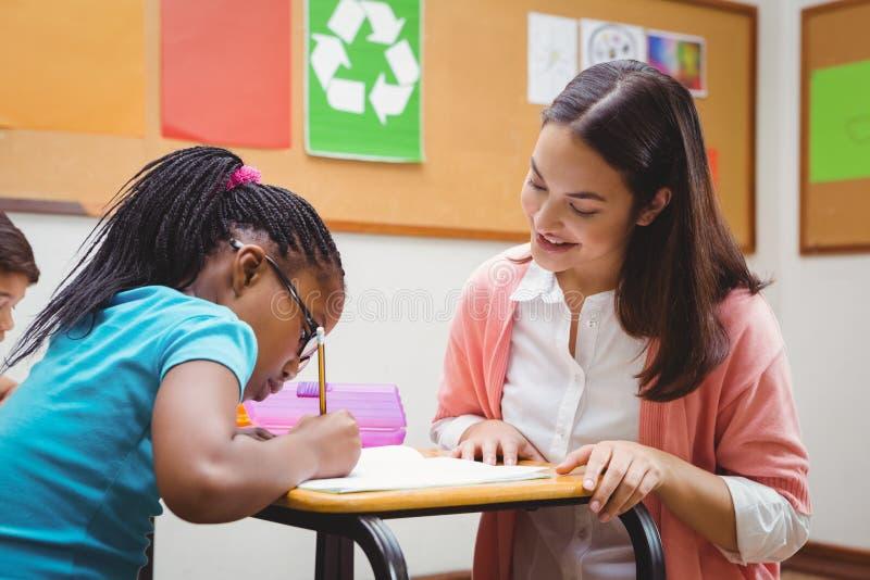 帮助她的学生的愉快的老师 免版税库存照片