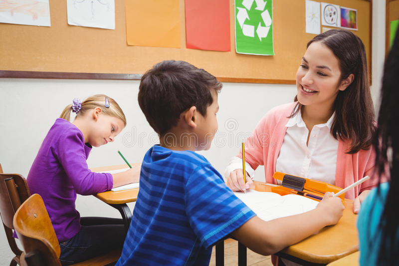 帮助她的学生的愉快的老师 库存照片