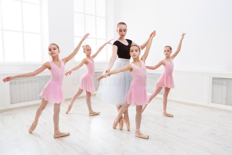 帮助她的学生的老师在舞蹈课期间 图库摄影